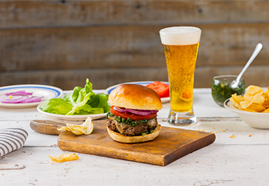 A thick chimichurri burger with melted cheese, lettus, tomato, red onion and bun on top of a wooden platter. A tall glass of American Pale Ale sits directly behind it